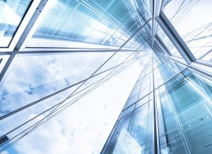 Photograph of towering glass buildings and a clouded blue sky